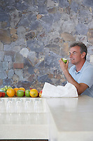 Mature man sitting at countertop eating apple
