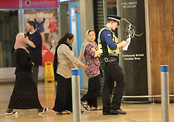 **MINIMUM FEE FOR USE - see  special instructions** © licensed to London News Pictures. London, UK. A group of woman are stopped and questioned by British Transport Police.. Organised groups of beggars use woman and young children to beg around shopping areas of west London. The groups use minors to approach men and woman leaving high end shops, asking for money . The children are well trained, targeting only wealthy looking people with middle eastern appearance. The women supervise the children from a few steps away. Photo credit: J.A/LNP