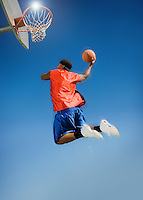 Basketball player shooting with ball low angle view
