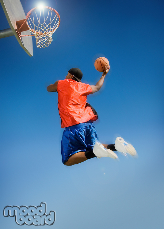 Basketball player shooting with ball low angle view