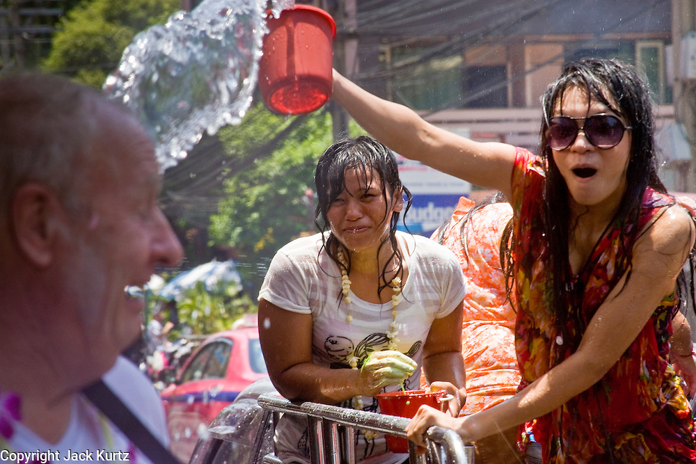 "Apr. 13, 2010 - Bangkok, Thailand: Thai women throw water at a tourist during Songkran festivities on a soi off of Sukhumvit Rd in Bangkok Tuesday. Songkran is the Thai New Year's holiday, celebrated from April 13 - 15. This year's official celebrations have been cancelled because of the Red Shirt protests but Thais are still marking the holiday. It's one of the most popular holidays in Thailand. Songkran originally was celebrated only in the north of Thailand, and was adapted from the Indian Holi festival. Except the Thais throw water instead of colored powder. The throwing of water originated as a way to pay respect to people, by capturing the water after it had been poured over the Buddhas for cleansing and then using this ""blessed"" water to give good fortune to elders and family by gently pouring it on the shoulder. Among young people the holiday evolved to include dousing strangers with water to relieve the heat, since April is the hottest month in Thailand (temperatures can rise to over 100°F or 40°C on some days). This has further evolved into water fights and splashing water over people riding in vehicles. The water is meant as a symbol of washing all of the bad away and is sometimes filled with fragrant herbs when celebrated in the traditional manner. Photo by Jack Kurtz"