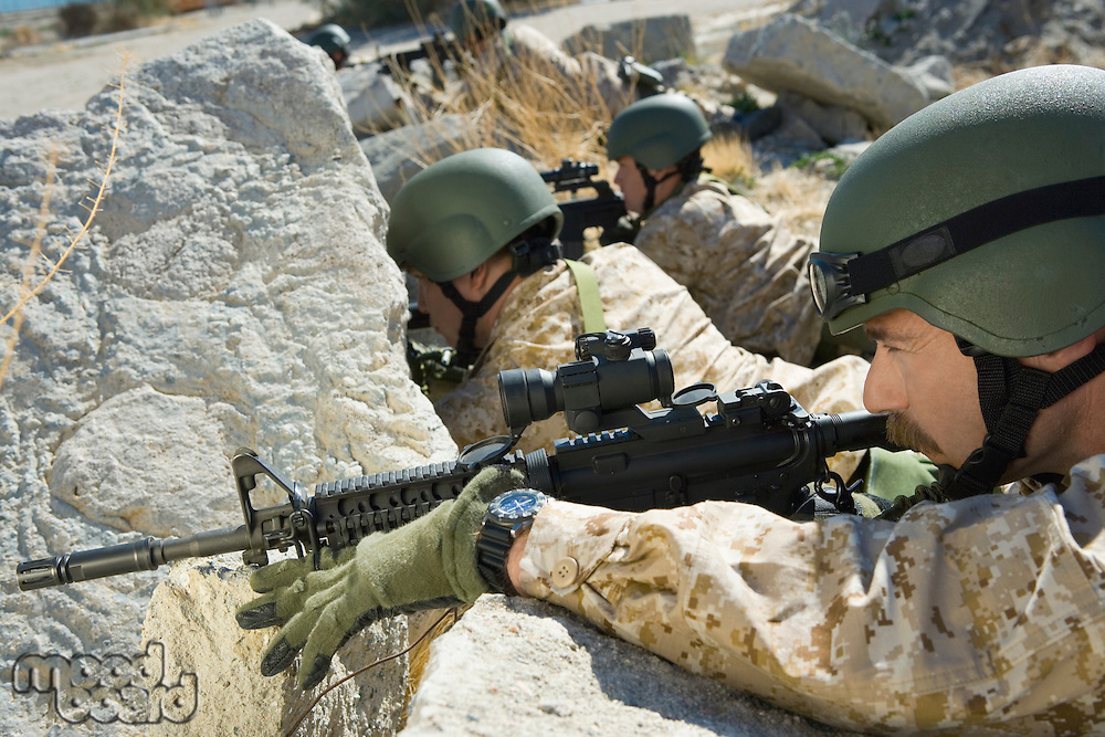 Soldiers with rifles hiding behind rocks