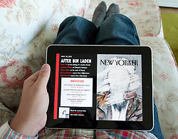 Man reading digital iPad version of New Yorker magazine