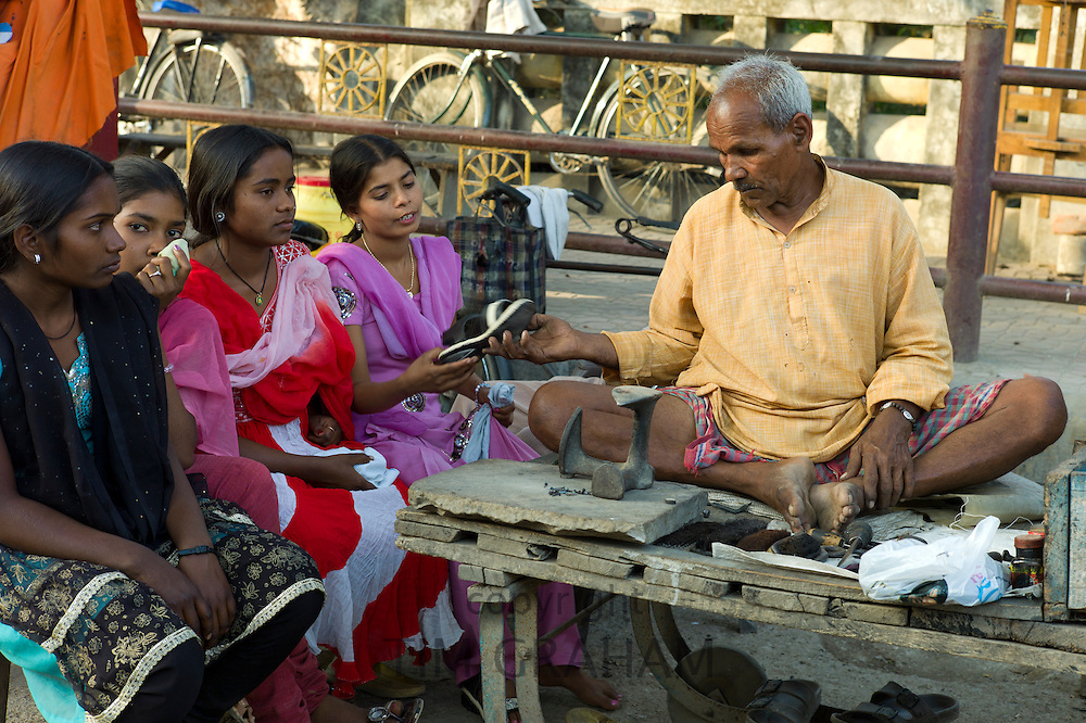Indian girls in shoe shop with cobbler at work at Sarnath near Varanasi, Benares, Northern India
