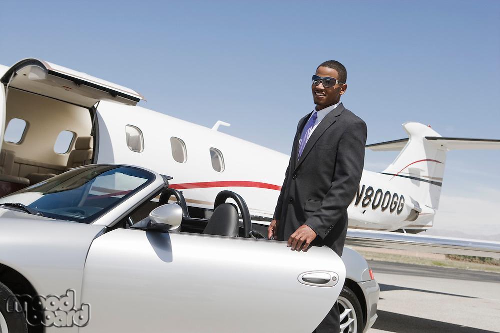 African-American businessman opening door of convertible on landing strip.