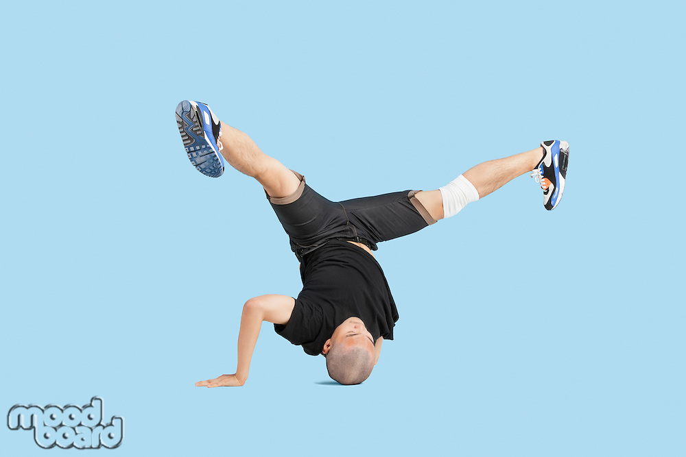 Male dancer doing head stand with legs spread apart over blue background