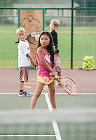 Sophia Moore, Jason Allen and Mason Sleeper practice their backhand swing during tennis lessons at Memorial Park Tuesday evening.  (Karen Bobotas/for the Laconia Daily Sun)