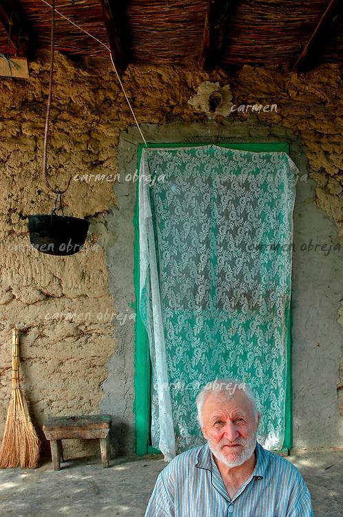 old sick man sitting on his verandah, Dobrogea region