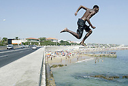 Portuguese Summer. A young man run from the road and dives into the sea off Carcavelos beach outskirts of Lisbon.