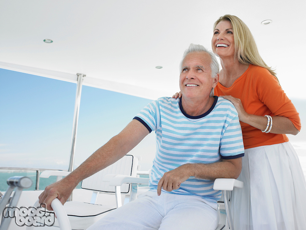 Smiling middle-aged couple at helm of yacht