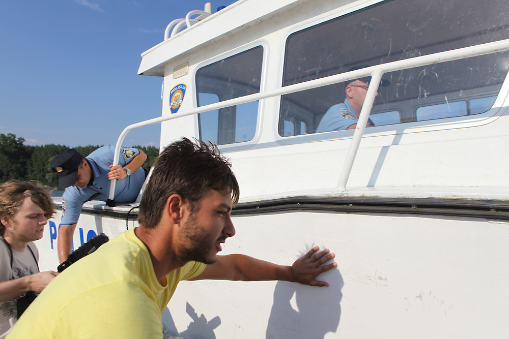 Alex Kahn, who has just managed to set foot on Liberty Island - part of Liberland - is pushing away the Liberland boat from the Croatian police boat trying to get the boat back into the Croatian waters so the Croatian police can arrest the Liberland boat's occupants.