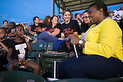 Mayor Lovely Warren and her daughter Taylor Granison, 5, sit with a group of students from School #17 at Frontier Field in Rochester on Friday, July 31, 2015. The students camped in tents on the field after the game.