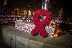 "© Licensed to London News Pictures . 01/12/2013 . Manchester , UK . A large red ribbon made up of dozens of red roses , placed on the city's Beacon of Hope AIDS memorial , in Sackville Park , surrounded by candles and cards . World AIDS Day commemoration in Sackville Park , Manchester , this evening (Sunday 1st December 2013) including a candle-lit procession around the city's "" Gay Village "" . Photo credit : Joel Goodman/LNP"