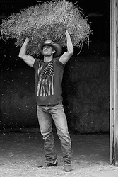 All American Cowboy holding a hay bale over his head in a barn