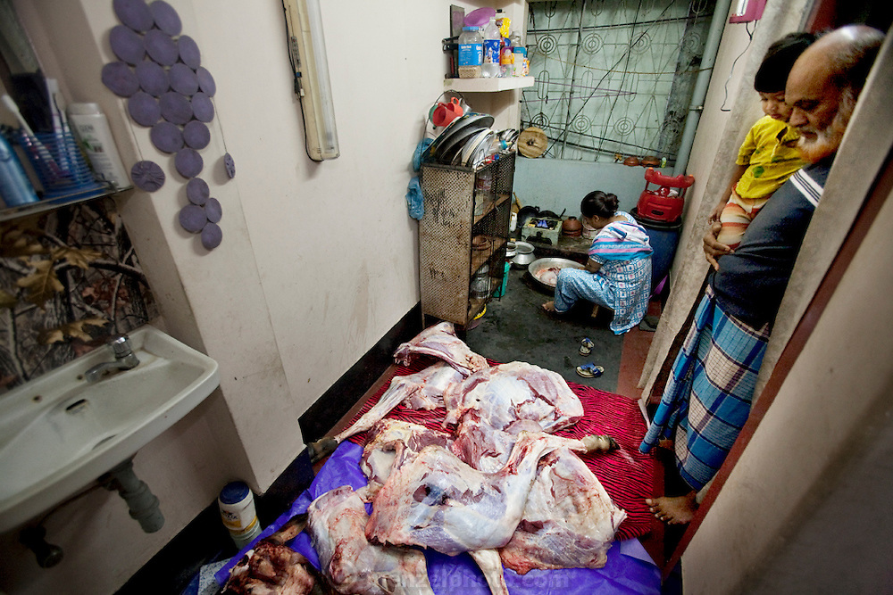 A woman prepares the meat of a butchered cow for the annual religious festival of Eid al-Adha. Bangladesh has the world's fourth largest Muslim population, and during the three days of Eid al-Adha, the Festival of Sacrifice, Dhaka's streets run red with the blood of thousands of butchered cattle. The feast comes at the conclusion of the Hajj, the annual Islamic pilgrimage to Mecca. In both the Koran and the Bible, God told the prophet Ibrahim (Abraham) to sacrifice his son to show supreme obedience to Allah (God). At the last moment, his son was spared and Ibrahim was allowed to sacrifice a ram instead. In Dhaka, as in the rest of the Muslim world, Eid al- Adha commemorates this tale, and the meat of the sacrificed animals is distributed to relatives, friends, and the poor.  .