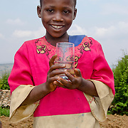 Cyuzuzo Francoise, a young girl in Rulindo District, Rwanda, holds a glass of safe drinking water.