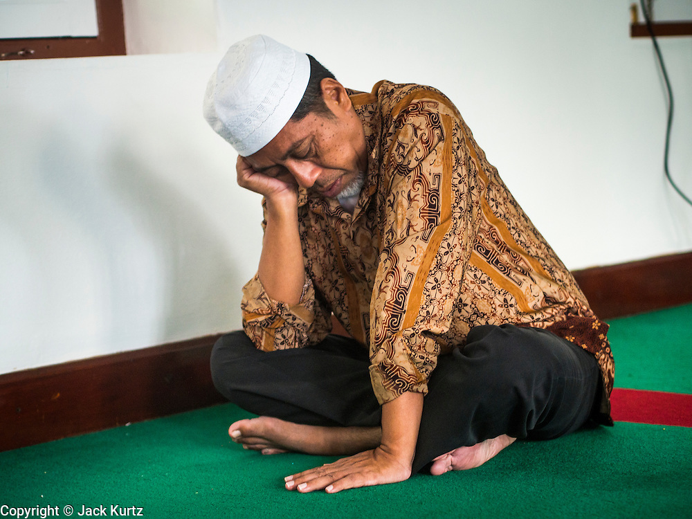 13 JULY 2013 - BANGKOK, THAILAND: A man prays in Haroon Mosque in Bangkok, Thailand, before Iftar (the Muslim meal that breaks the day long fast) during Ramadan. Ramadan is the ninth month of the Islamic calendar, and the month in which Muslims believe the Quran was revealed. The month is spent by Muslims fasting during the daylight hours from dawn to sunset. Fasting during the month of Ramadan is one of the Five Pillars of Islam. Muslims believe that the Quran was sent down during this month, thus being prepared for gradual revelation by Jibraeel (Gabriel) to the prophet Muhammad.        PHOTO BY JACK KURTZ