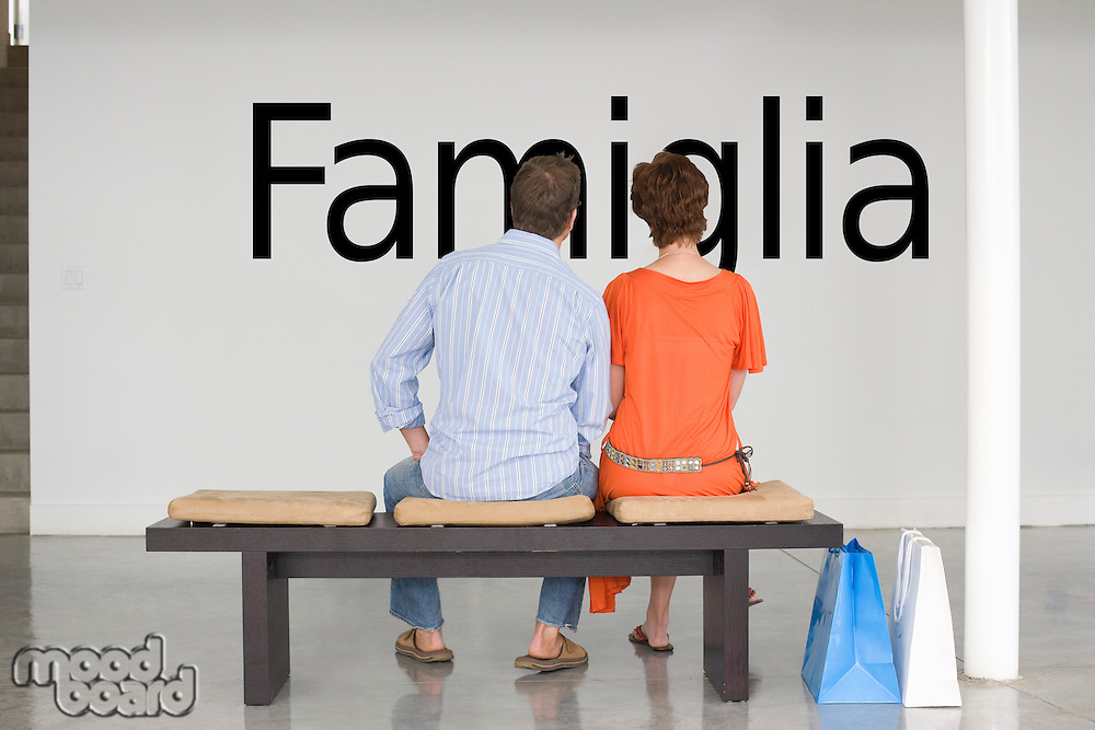 Rear view of couple seated on bench reading Italian text on wall
