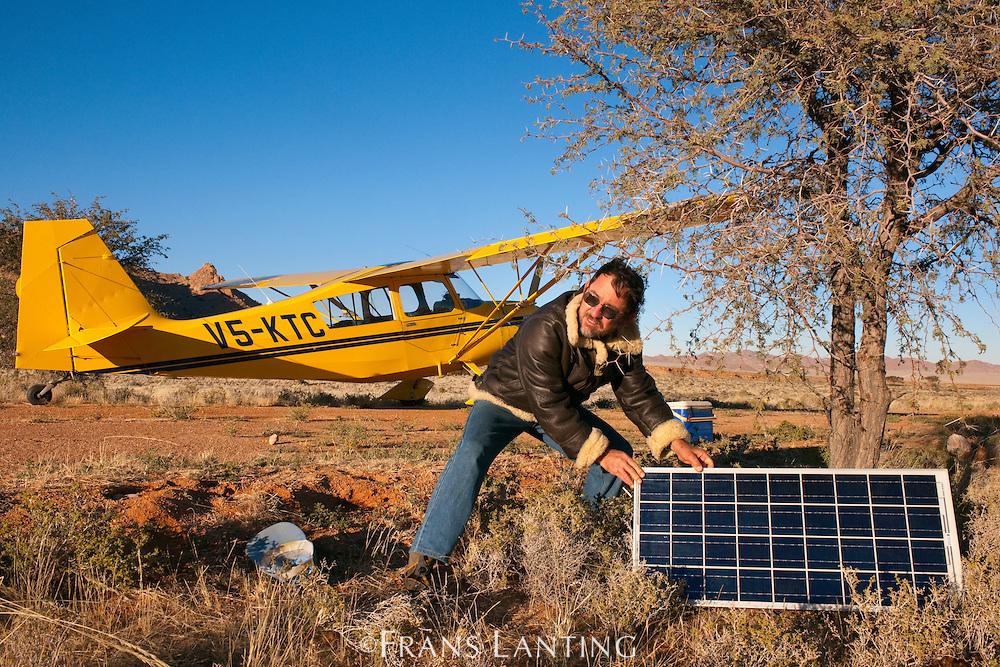 Bush pilot Gino Noli deploying solar panel to jump start plane on cold morning, Aus, Namibia