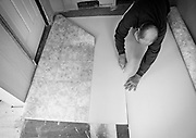 Mike cuts out a piece of linoleum for the halfway house property that he manages, Tuesday, Jan. 8, 2013. Of the fifty ex-convicts that have been through Mike's properties in the past five years, only four have returned to prison. And even the four offenders who were re-admitted to the penal system were brought back in for parole violations and not for new criminal charges.