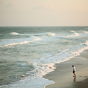 A man walks near the waves at Wrightsville Beach, NC...