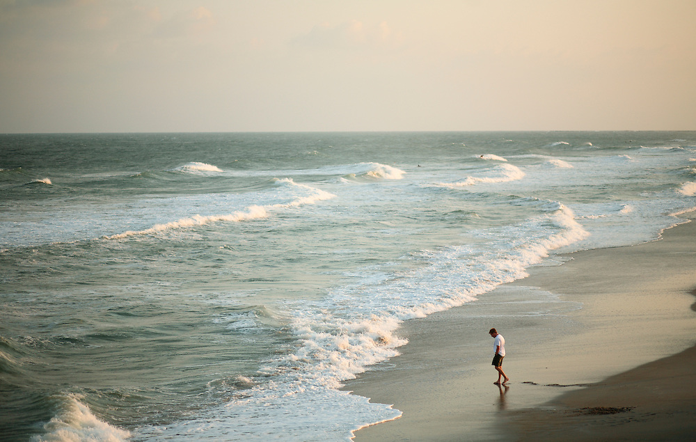 A man walks near the waves at Wrightsville Beach, NC...