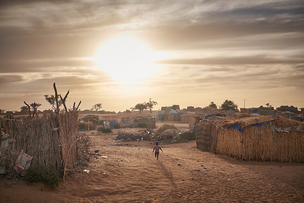 A young child runs through a camp of displaced people in the neighbourhood of Chateau, Diffa, Niger on February 13, 2016. The camp is mixed between displaced people from Niger, Nigeria and Chad. They have fled attacks by the militant group Boko Haram on their villages and it's ongoing conflicts with the armies of each country. Caritas undertook a distribution of mosquito nets, cooking pots, sleeping covers, hygiene kits, clothes and cash transfers to the displaced. 228 households received support from Caritas among an estimated 1500 households in the  vicinity of Chateau. There is still great need. There is no school system in place for the children and the housing is not adequate for many as more people arrive each day escaping hostilities.
