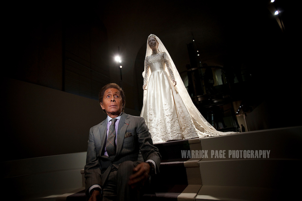 Fashion designer Valentino Garavani sits next to his exhibit of Princess Marie-Chantal of Greece's pearl-encrusted ivory silk wedding gown, at the 'Valentino: Master of Couture' exhibition at Somerset House on November 28, 2012 in London, United Kingdom. Celebrating the life and work of the Italian master couturier, the show features over 130 hand crafted designs worn by Hollywood icons and Royalty. The exhibition runs from November 29, 2012 - March 3, 2013. (Photo by Warrick Page)