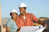 Couple over blueprint in construction site