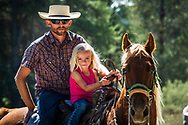 A father, daughter and horse pause from a cattle drive for a portrait. <br /> <br /> Note; none of my western images are to be used for anti-ranching advocacy.