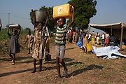Central African Republic / Akadus Zangoa, 10 years old carries a container of water at the international airport in Bangui on December 15, 2013. His mother is running a stall selling various items to make a living while sheltering at the airport. There are 35,000 IDPs sheltering here having fled violence between anti-Balaka fighters and Seleka rebels with parents, children and siblings a week before. On the morning of Thursday 5th, December Christian anti-balika militants entered the city and attacked Seleka rebels. Over the days that followed hundreds of people were killed. The Seleka made up of a muslim majority with many of the rebels originating from northern Central African Republic, Sudan and Chad brought to power a new president Michel Djotodia, a former Seleka leader in a March 24, 2013 coup.  The political establishment has failed to control the armed group that has wreaked havoc, including murdering, looting and burning of villages on the civilian population with mass displacements resulting.UNHCR / S. Phelps / December 2013