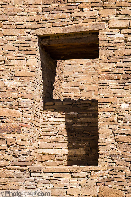 A stone wall window opening creates an almost S-shaped shadow. Pueblo Bonito is a monumental public building (Puebloan Great House) occupied from around 828 to 1126 AD, now preserved at Chaco Culture National Historical Park, New Mexico, USA. The huge D-shaped complex of Pueblo Bonito enclosed two plazas with dozens of ceremonial kivas, plus 600 rooms towering 4 and 5 stories above the valley floor. The functions of this building included ceremony, administration, trading, storage, hospitality, communications, astronomy, and burial, but few living quarters. Chaco Culture NHP hosts the densest and most exceptional concentration of pueblos in the American Southwest and is a UNESCO World Heritage Site, located in remote northwestern New Mexico, between Albuquerque and Farmington. From 850 AD to 1250 AD, Chaco Canyon advanced then declined as a major center of culture for the Ancient Pueblo Peoples. Chacoans quarried sandstone blocks and hauled timber from great distances, assembling fifteen major complexes that remained the largest buildings in North America until the 1800s. Climate change may have led to its abandonment, beginning with a 50-year drought starting in 1130.