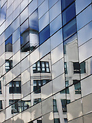 Classic building with water towers as reflected in the windows and stainless steel panels of a new building along the High Line Park in New York, NY. Past, present and future architecture!