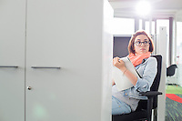 Businesswoman holding notepad while sitting on chair at creative office