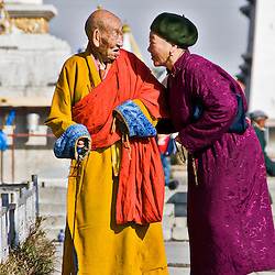 Woman talking to a Buddhist monk at the Gandantegchinlen Khiid monastery, Ulaan Bataar, Mongolia.