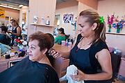 July 25 - PHOENIX, AZ: GUADALUPE VALENCIA has her hair done by MARICELA RODRIGUEZ at El Gran Mercado. Rodriguez said she's been styling hair at the market for eight years and has never seen business as slow as it is now. El Gran Mercado (The Big Market) in Phoenix is the largest flea market in the Phoenix area and has served the area's immigrant community for more than 20 years. With more than 150 small independent stalls selling Mexican clothes, cowboy hats, Mariachi music and food stalls selling Mexican favorites like birria chivo (goat stew) and menudo (tripe) it was more like a Mexican market than an American mall. Business in the mercado is down more than half this year because many immigrant families, legal and illegal, are leaving Arizona before the state's tough new anti-immigrant law, SB 1070 goes into effect on July 29. SB 1070 allows local police officers to check the immigration status of people they have probable cause to believe may be in the US illegally and requires immigrants to carry their immigration papers with them at all times.    Photo by Jack Kurtz