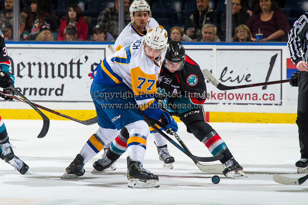 KELOWNA, CANADA - DECEMBER 1: Kirby Dach #77 of the Saskatoon Blades wins the face off against Kyle Topping #24 of the Kelowna Rockets on December 1, 2018 at Prospera Place in Kelowna, British Columbia, Canada.  (Photo by Marissa Baecker/Shoot the Breeze)