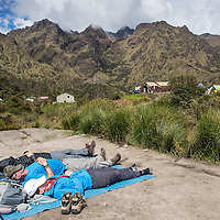 Peru, Backpackers resting in sunshine at campsite near Sayaqmarka ruins along Inca Trail to Machu Picchu