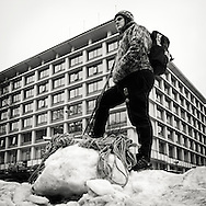 Mountain climber standing on Pile of snow in central square of Bergen Norway