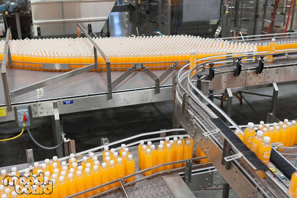 Orange juice bottles on conveyor belt in bottling plant