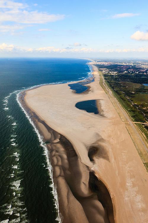 Nederland, Zuid-Holland, Gemeente Westland, 15-07-2012; Delflandse Kust ter hoogte van Ter Heijde en Monster, Den Haag aan de horizon..De Zandmotor is een kunstmatig schiereiland ontstaan door het opspuiten van zand voor de kust. Wind, golven en stroming zullen het zand langs de kust verspreiden waardoor breder stranden en duinen ontstaan. De zandmotor is een experiment in het kader van kustonderhoud en kustverdediging. .Sand Engine, artificial peninsula build by the raising of sand for the coast of Ter Heijde (near the Hague, at the horizon). Wind, waves and currents will distribute the sand along the coast yielding wider beaches and dunes along the coastline. The Sand Engine is a experiment for coastal maintenance of coastal defense..luchtfoto (toeslag); aerial photo (additional fee required) foto Siebe Swart / photo Siebe Swart