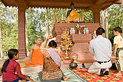 19 MARCH 2006 - SIEM REAP, SIEM REAP, CAMBODIA: Buddhist monk blessing a family at a contemporary temple within the environs of the Angkor Wat complex. Angkor Wat, which was built in stages through the 1400s, is the most popular tourist attraction in Cambodia and is expected to draw one million foreign visitors in 2006. It is still in use as Buddhist temple complex and life goes on in the monasteries around Angkor Wat despite the hordes of tourists tramping through the site.  Photo by Jack Kurtz / ZUMA Press