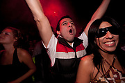 YOUNG MALE CLUBBERS WITH ARMS IN THE AIR FEMALE IN SUNGLASSES SMILING AT CAMERA