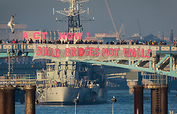 © Licensed to London News Pictures. 20/01/2017. London, UK. A banner is suspended from Tower Bridge as part of the 'Bridges not Walls' campaign of national demonstrations against Donald Trump's presidency. Donald Trump will attend his inauguration ceremony in Washington today. Photo credit: Peter Macdiarmid/LNP