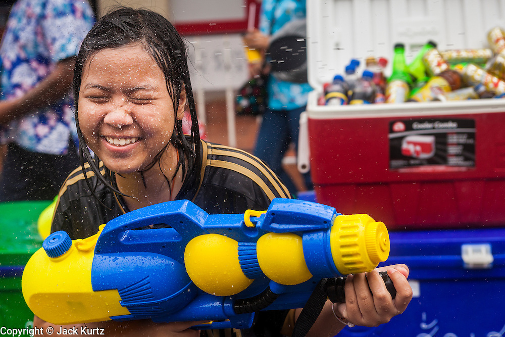 13 APRIL 2014 - BANGKOK, THAILAND:  A Thai child with a large squirt gun on Khao San Road, Bangkok's backpacker district, during Songkran water fights. Songkran is celebrated in Thailand as the traditional New Year's Day from 13 to 16 April. Songkran is in the hottest time of the year in Thailand, at the end of the dry season and provides an excuse for people to cool off in friendly water fights that take place throughout the country. Songkran has been a national holiday since 1940, when Thailand moved the first day of the year to January 1.    PHOTO BY JACK KURTZ