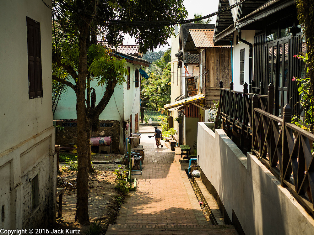 """13 MARCH 2016 - LUANG PRABANG, LAOS: A woman crosses a restored alley in a residential section of Luang Prabang. Luang Prabang was named a UNESCO World Heritage Site in 1995. The move saved the city's colonial architecture but the explosion of mass tourism has taken a toll on the city's soul. According to one recent study, a small plot of land that sold for $8,000 three years ago now goes for $120,000. Many longtime residents are selling their homes and moving to small developments around the city. The old homes are then converted to guesthouses, restaurants and spas. The city is famous for the morning """"tak bat,"""" or monks' morning alms rounds. Every morning hundreds of Buddhist monks come out before dawn and walk in a silent procession through the city accepting alms from residents. Now, most of the people presenting alms to the monks are tourists, since so many Lao people have moved outside of the city center. About 50,000 people are thought to live in the Luang Prabang area, the city received more than 530,000 tourists in 2014.    PHOTO BY JACK KURTZ"""
