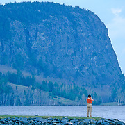 Woman taking photographs of Mount Kineo on Moosehead Lake