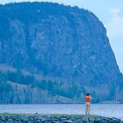 Woman taking photographs of Mount Kineo on Moosehead Lake