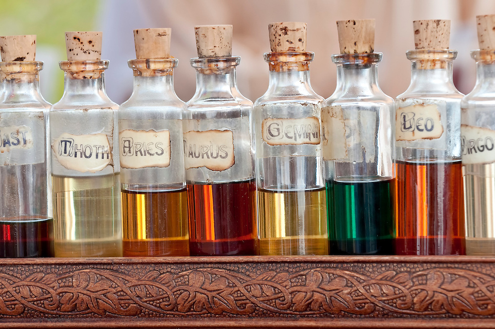 Bottles with basics oils, essentials and fragances aligned in a street market.