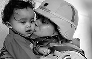 Emily Crespo kisses her one-year-old son Mathew Troche goodbye as she and other members  of the 50th Main Support Battalion deploy for Iraq. She is leaving all four of her children for a year.